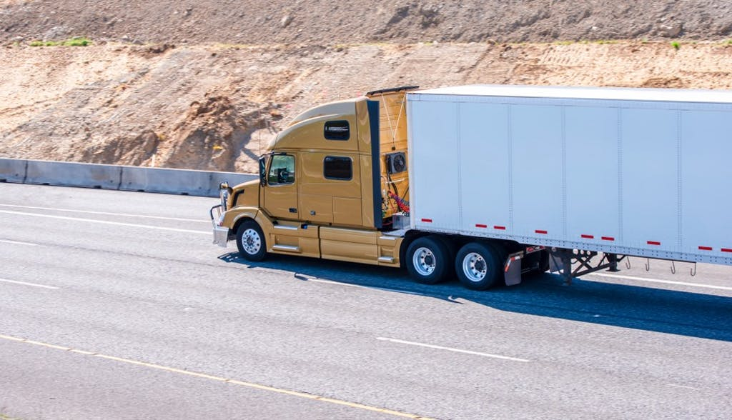 Yellow truck hauling a dry van trailer